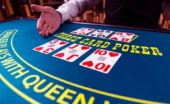 Dealer reveals cards in three card poker